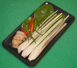 Lemon grass, lime leaves, chilli, and galangal in a cling-wrapped styrofoam tray