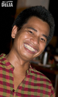 A Thai waiter smiles for the camera