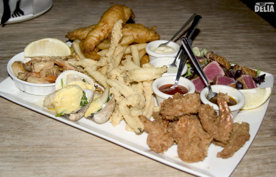 A seafood platter with various fish, shellfish, chips and dips