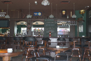 A long bar, lots of empty seats and tables and a high ceiling in Shenanigans on Penang Island, Malaysia