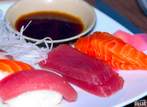 Sashimi and sushi with a bowl of soy sauce