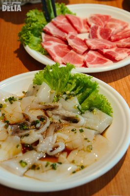 Slices of pork neck and marinated squid ready for cooking