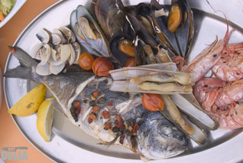 A silver bream on a seafood platter with prawns, clams, razor clams and mussels