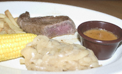 Cold (and undercooked) steak, frozen fries, watery peppercorn sauce (no peppercorns in evidence), pale, greasy onions and corn-on-the-cob on a white plate