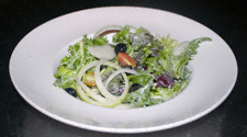 Salad with leaves, salad onion rings, black olives and dressing