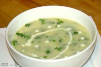 Close-up of a bowl of leek and potato soup with extra herbs and a swirl of fresh cream