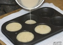 Batter being poured into a Yorkshire pudding