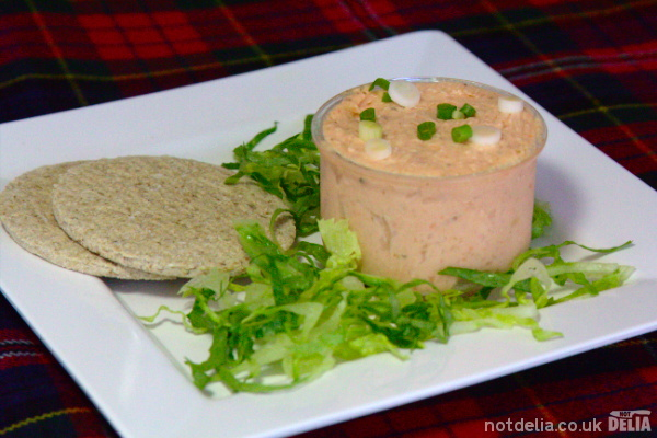 Smoked salmon paté on a plate with oatcakes and shredded lettuce garnish