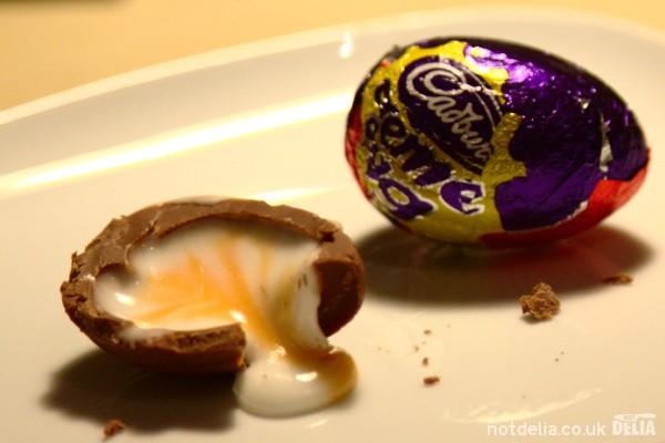 Half a Cadbury Creme Egg next to an unwrapped one